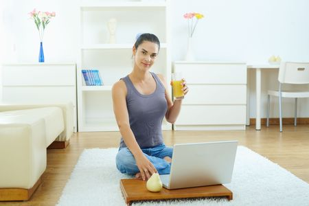 Casual young woman using laptop computer, sitting on floor in living room. photo