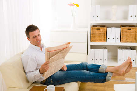 Casual man wearing white shirt and jeans, sitting on couch barefooted and reading newspaper. Stock Photo - 6235749
