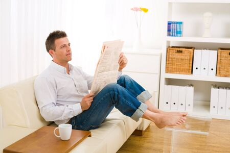 Casual man wearing white shirt and jeans, sitting on couch barefooted and reading newspaper. photo