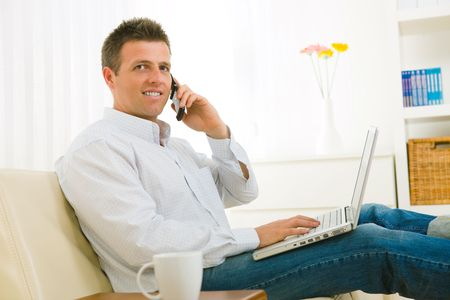 Casual businessman working at home sitting on couch, using laptop computer, talking on mobile phone. photo