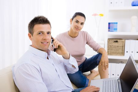 Young couple using laptop computer at home, sitting on couch. Man talking on mobile phone. Selective focus on man. Stock Photo - 6235836