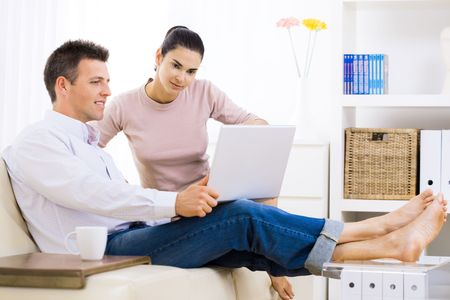 Young couple browsing internet at home, using laptop computer, sitting on couch, smiling. Stock Photo - 6235804