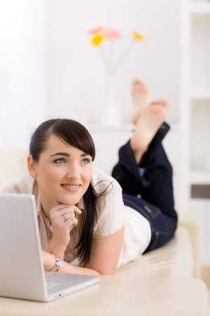 Young women is resting on the couch at home and surfing the internet on her laptop computer. Stock Photo - 6235770