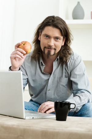 Casual man using laptop computer at home, sitting at couch, holding apple. photo