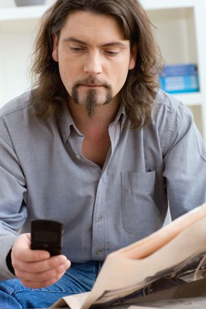 busy beard: Man using mobile phone and holding newspaper in hand, sitting in living room at home.
