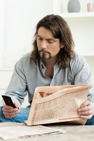 Man using mobile phone and holding newspaper in hand, sitting in living room at home. Stock Photo - 6235838