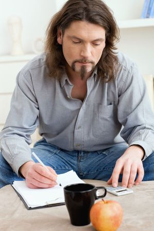 Man using digital calculator and writing notes or calculations on paper. photo