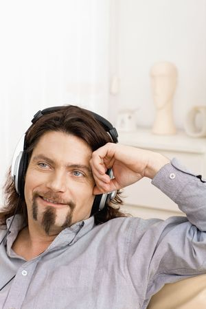 Casual man sitting on couch at home and listening music with headphones, smiling. photo