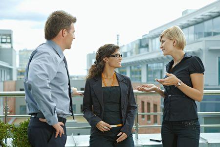 Geschäftsleute haben Pause und sprechen auf Terrasse des Bürogebäudes.