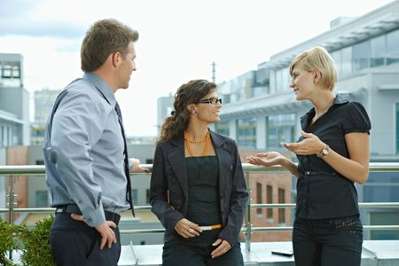 attire: Business people having break and talking on terrace of office building. Stock Photo