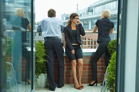 Business people having break on terrace of office building, businesswoman talking on mobile phone. photo