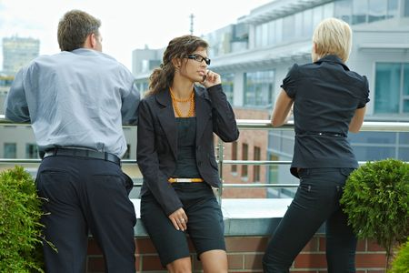 Business people having break on terrace of office building, businesswoman talking on mobile phone. photo