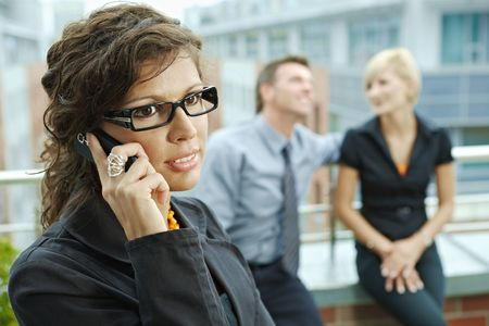 Business people talking on terrace outdoor of office building. Businesswoman in front using mobile phone. photo