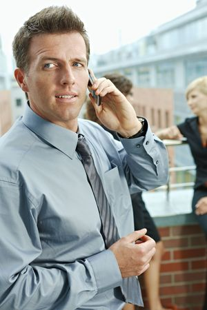 Business people talking on terrace outdoor of office building. Businessman in front using mobile phone. photo
