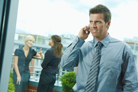 Business people talking on terrace outdoor of office building. Businessman in front using mobile phone. Through the window view. photo