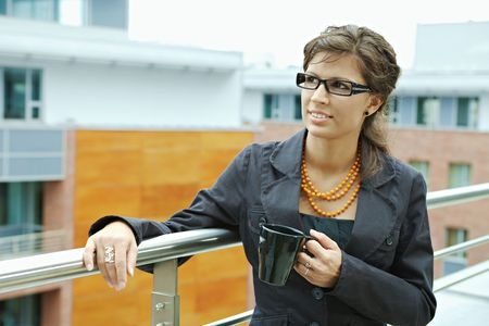 Businesswoman having break on office terrace outdoor drinking coffee. photo
