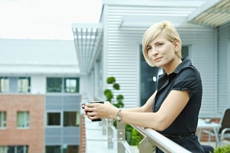 Businesswoman having break on office terrace outdoor drinking coffee. Stock Photo - 6254333