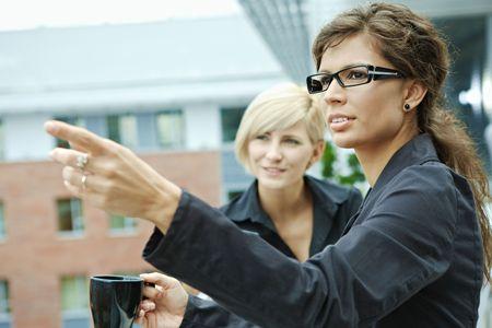 Businesswomen having break on office terrace outdoor drinking coffee. photo