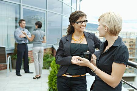 having a break: Businesswomen having break on office terrace outdoor drinking coffee talking.