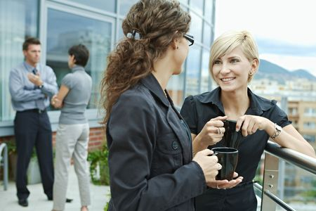 interacting: Businesswomen having break on office terrace outdoor drinking coffee talking.