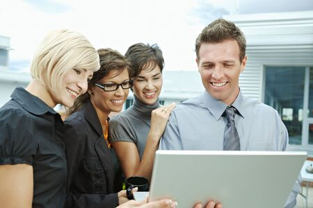 Team of business people looking at laptop computer outdoor in front of office building. Stock Photo - 6254345