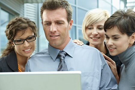 Team of business people looking at laptop computer outdoor in front of office building. Stock Photo - 6254415