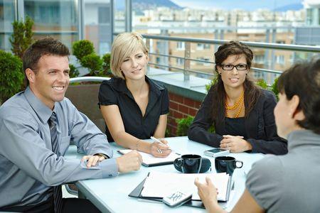 n�gociation: Groupe des jeunes gens d'affaires assis autour de la table sur la terrasse ext�rieure de bureau, parler et travailler ensemble.