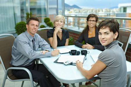ropa casual: Grupo de j�venes empresarios sentados alrededor de la mesa en la terraza de la Oficina al aire libre, hablando y trabajando juntos.