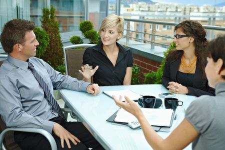 Group of young business people sitting around table on office terrace outdoor, talking and working together. photo