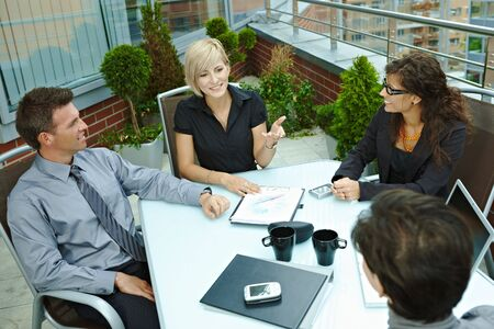 overhead: Group of young business people sitting around table on office terrace outdoor, talking and working together.