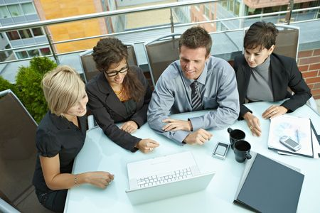Group of young business people sitting around table on office terrace outdoor, talking and working together. Overhead view. Stock Photo - 6254399