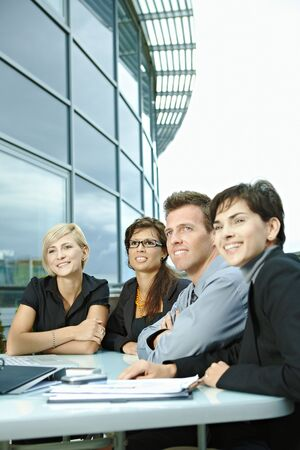 Group of young business people sitting in a row at table on office terrace outdoor, talking and working on laptop computer. Stock Photo - 6254317