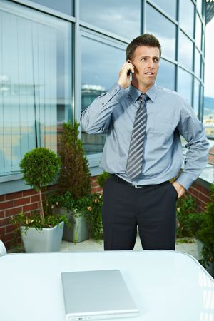 officetower: Serious businessman standing outdoor talking on mobile phone, looking away.