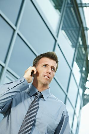 Serious businessman standing outdoor talking on mobile phone, looking away. Stock Photo - 6254371