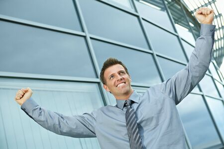 Happy successful businessman raising arms outdoor, smiling. Stock Photo - 6254397