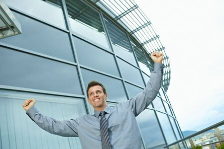 officetower: Happy successful businessman raising arms outdoor, smiling.