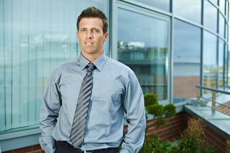 Businessman standing on office terrace outdoor, looking at camera, smiling. Stock Photo - 6254334