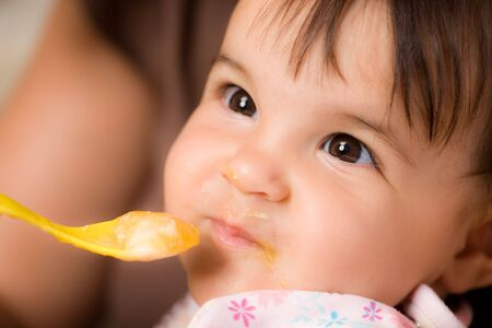 Mother feeding baby girl with spoon. photo