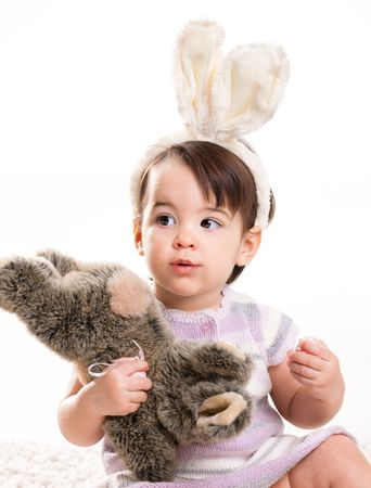 Baby girl in easter bunny costume, playing with toy rabbit, smiling. Isolated on white background. photo