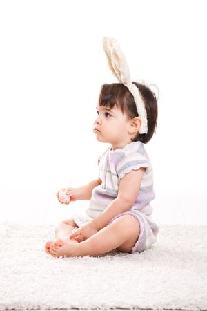 Profile portrait of baby girl with bunny ears headband, playing with easter eggs, isolated on white background. photo