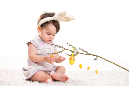 Baby girl in easter bunny costume, playing with easter eggs hanging from willow branch. Isolated on white background. Stock Photo - 6254470