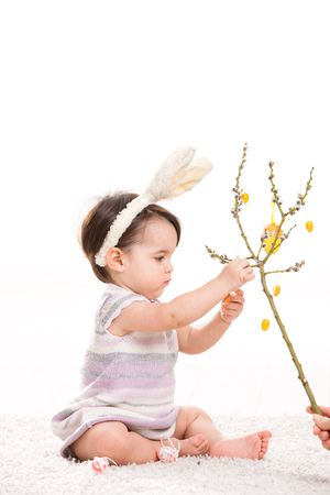 Baby girl in easter bunny costume, playing with easter eggs hanging from willow branch. Isolated on white background. photo