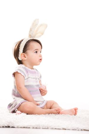 Portrait of baby girl with bunny ears headband, playing with easter eggs, isolated on white background. photo