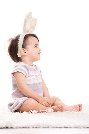 Profile portrait of baby girl with bunny ears headband, sitting on carpet. Isolated on white background. photo