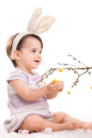 Baby girl in easter bunny costume, playing with easter eggs hanging from willow branch, smiling. Isolated on white background. photo