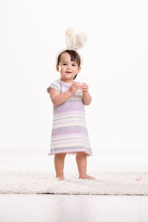 Happy baby girl in easter costume standing on carpet, playing with easter eggs, smiling. Isolated on white background. Stock Photo - 6254448