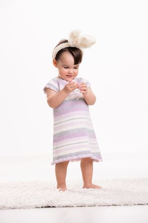 Happy baby girl in easter costume standing on carpet, playing with easter eggs, smiling. Isolated on white background. photo