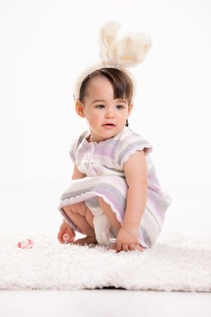 Baby girl with bunny ears headband, crouching on carpet, playing with easter eggs. Isolated on white background.