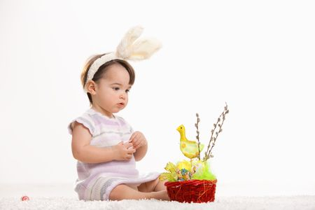 Baby girl in easter bunny costume, sitting on carpet and looking to easter basket. Isolated on white background. photo
