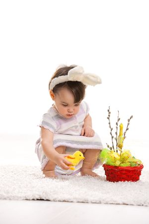 Baby girl in easter bunny costume, playing with toy chicken beside easter basket. Isolated on white background. photo